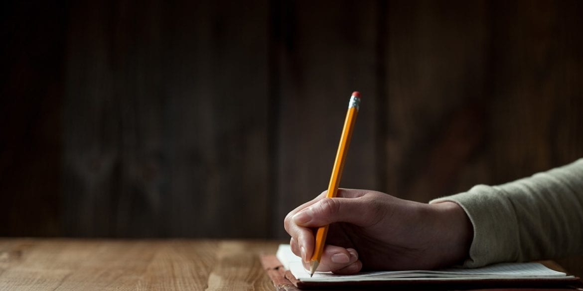 Hand writing notes with a pencil in a dark room