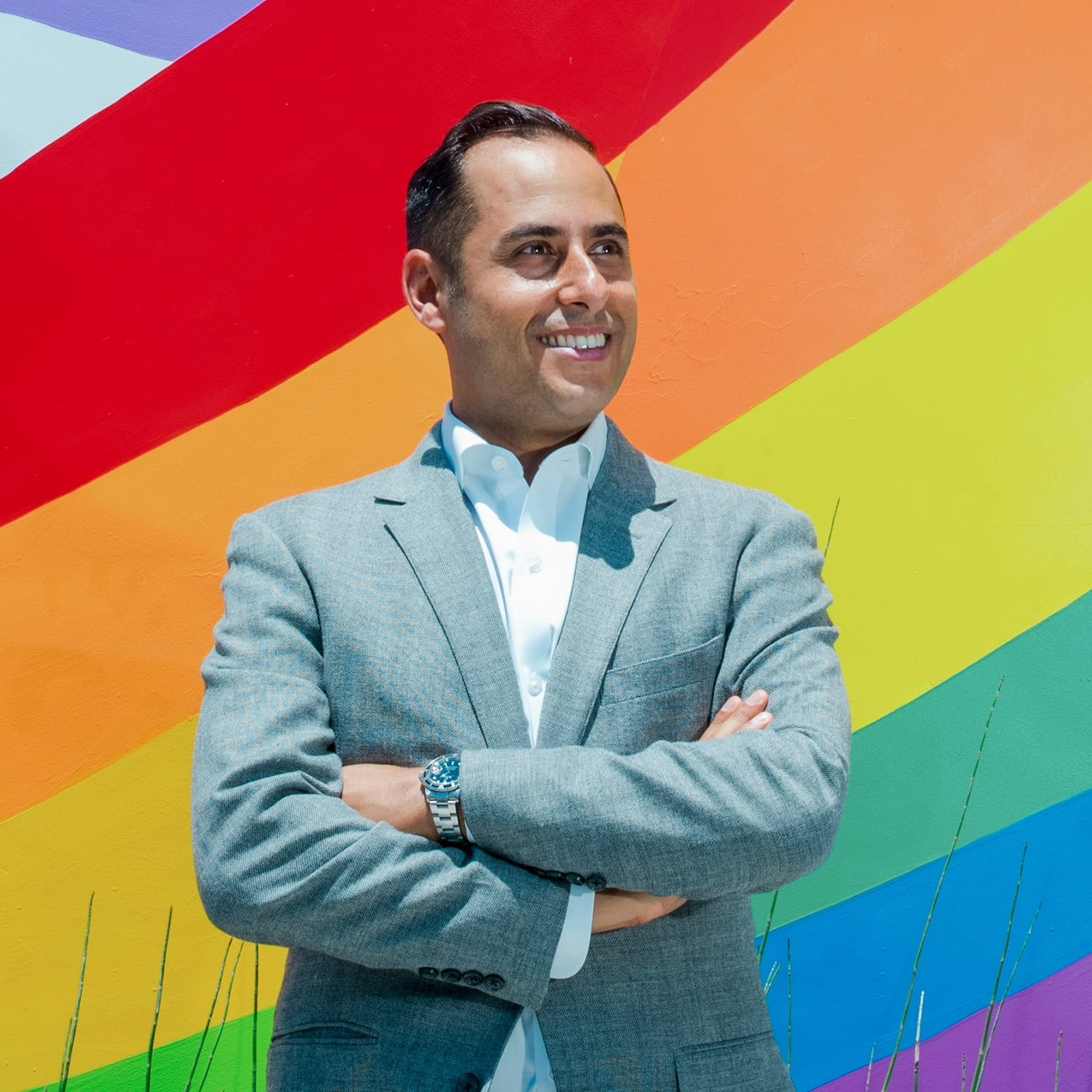 Raymond Hekmat in front of a rainbow mural